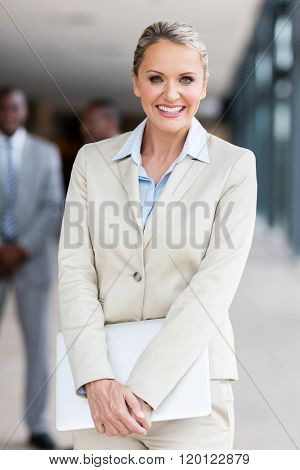 pretty businesswoman holding laptop in office
