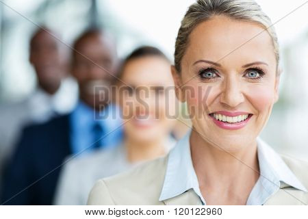 portrait of pretty mid age businesswoman with colleagues standing in a row