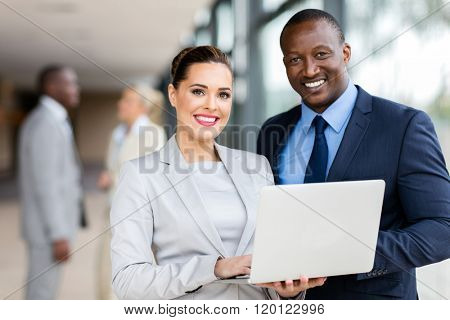 portrait of young colleagues using laptop computer