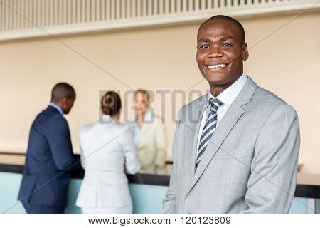 handsome african american manager standing at hotel reception
