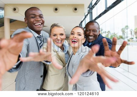 group of cheerful multiracial businesspeople reaching for the camera