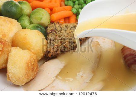 Roast chicken dinner with gravy being poured.