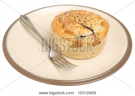 Individual meat pie decorated with poppy seeds