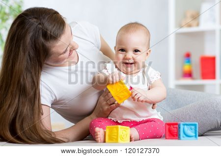 Mother and baby girl playing with color developmental toys in nursery