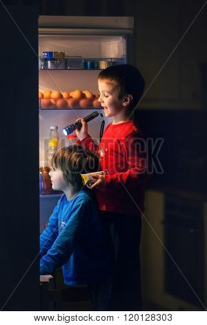 Two Little Boys, Secretly Eating Sweets From The Fridge At Night