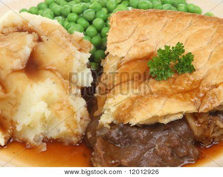 Steak pie with mashed potato, peas and gravy.