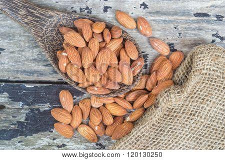almond on wooden spoon with hemp sacks on old wooden