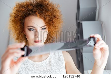 Closeup of attractive curly young female photographer holding and looking at photographic film