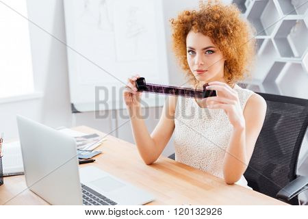 Pretty redhead young woman photographer sitting in office and looking through photographic film