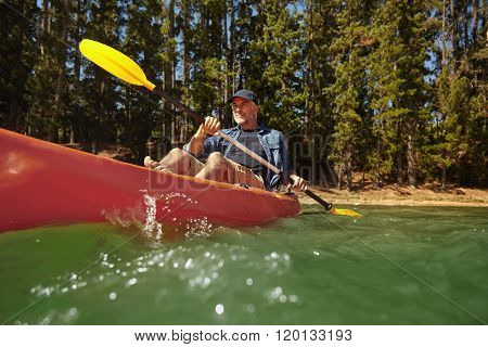 Mature Man Paddling A Kayak In A Lake