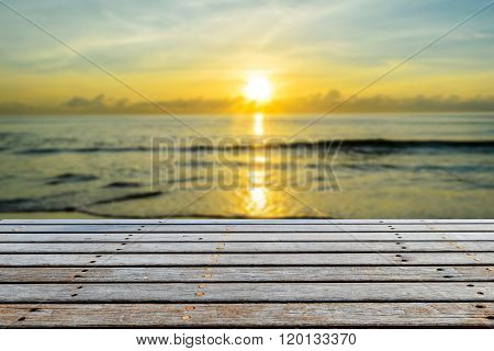 Wood table top on blurred beach with sunrise background for presentation product.
