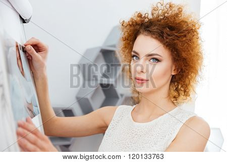 Smiling curly redhead young woman photographer put photos on whiteboard in office