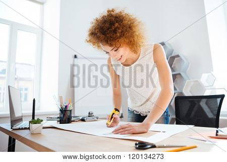 Smiling redhead young woman photographer using stationery knife and cutting sheet of paper in office