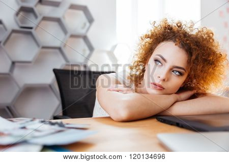 Attractive thoughtful curly woman designer sitting and dreaming on workplace in office