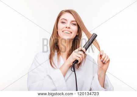 Cheerful attractive young woman straightening her hair with hair straightener over white background