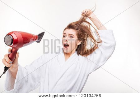 Funny frightened young woman in bathrobe  drying her hair and scared of dryer over white background