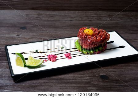 juicy Tartar of beef served with lime on white dish