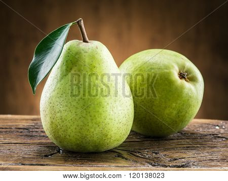 Two pears with leaf on wooden background.