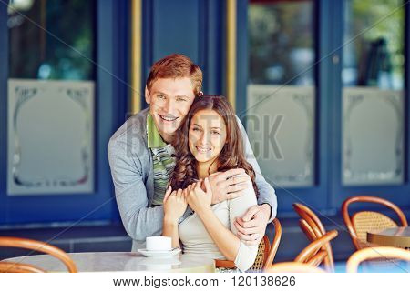 Affectionate couple sitting in caf�© and embracing