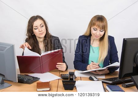 Two Business Women Working In The Office With One Desk