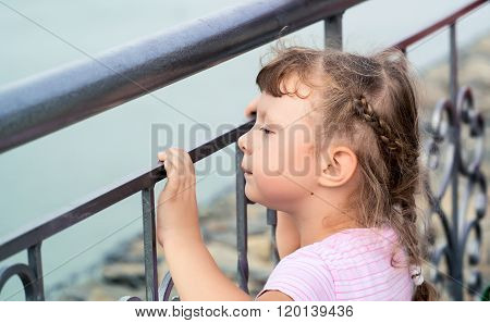 Girl Grieves At The Metal Fence