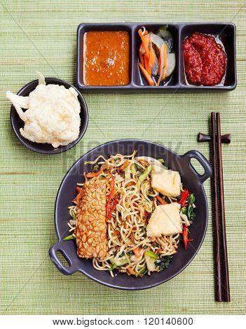 Mi goreng,mee goreng Indonesian cuisine, spicy stir fried noodles and assortment of asian sauces Top