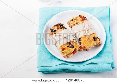 Granola, oatmeal, oat bars with dried cranberry and raisin on a white and blue background. Healthy b