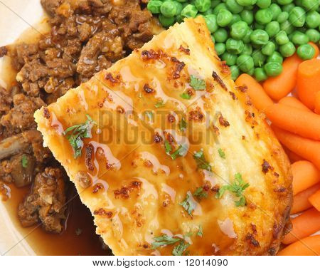 Shepherd's pie with peas, carrots and gravy.