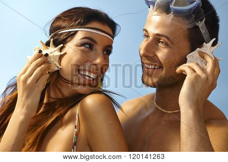 Closeup portrait of happy loving couple listening to murmur of sea in seashell at summertime.