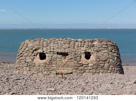 Stone structure built on Porlock Weir beach Somerset uk in summer