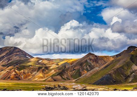 Travel to Iceland in the summer. National Park Landmannalaugar. Multicolored rhyolite mountains of the July sun lit