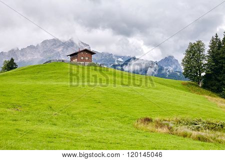 Traditional alpine hut against lush meadow and mountains - Alps beauty concept