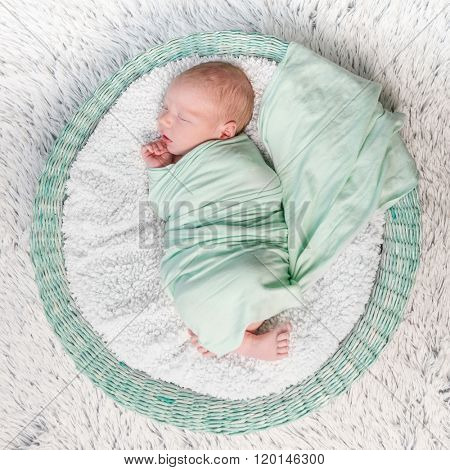 sweet newborn wrapped in a nappy sleeping on a round rug top view