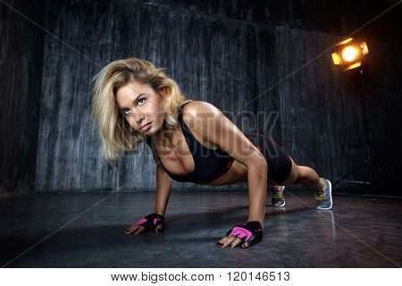 Beautiful muscular woman doing exercise  on a gray background