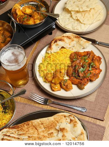 Indian chicken jalfrezi curry meal with Bombay aloo and pilau rice.