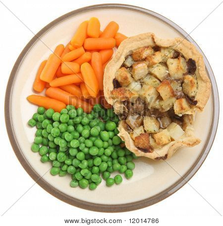 Individual shepherd's pie with peas carrots and gravy.