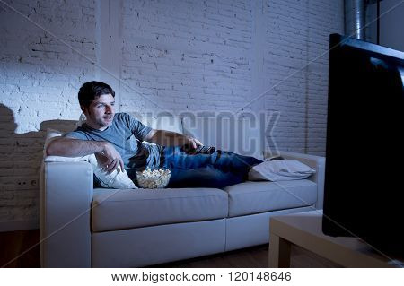 young attractive man at home lying on couch at living room watching tv holding remote control and changing channel or volume looking interested and excited with comedy movie or sitcom
