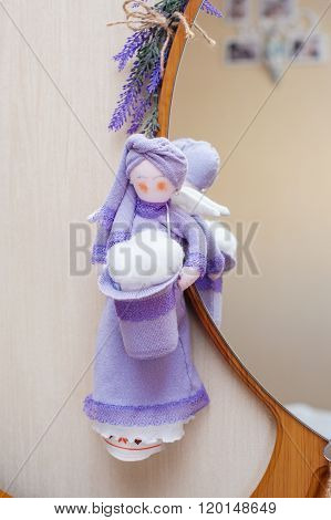 Rag doll hanging on the mirror in room