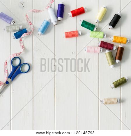 white wooden planks background with colorful thread skeins with text space