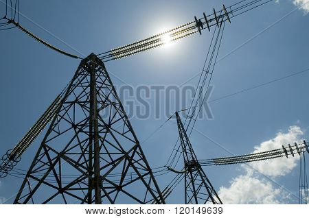 High-voltage Power Line Pylons Against Blue Sky Background