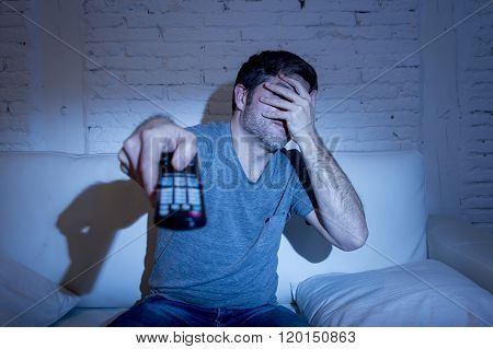 young man holding tv remote control sitting at living room couch watching television blocking his eyes with hand blinding himself while enjoying horror movie