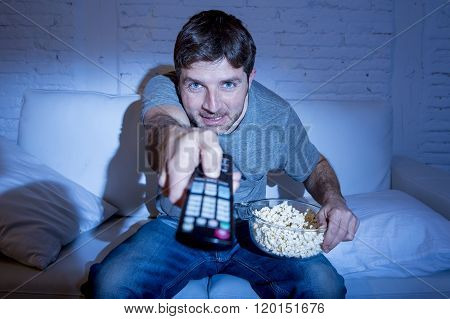 young attractive man at home lying on couch at living room watching tv eating popcorn bowl using remote control and changing channel or volume looking interested and excited in television fan concept