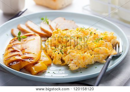 Eggs Scrambled, omelet with grilled bell sweet pepper and hot smocked chicken, ham in a plate on a w