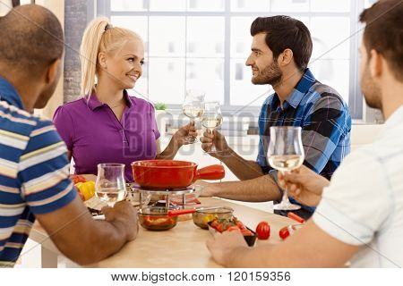 Happy friends clinking glasses, enjoying meal together.