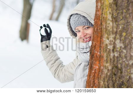 Girl snowball fighting in winter time.