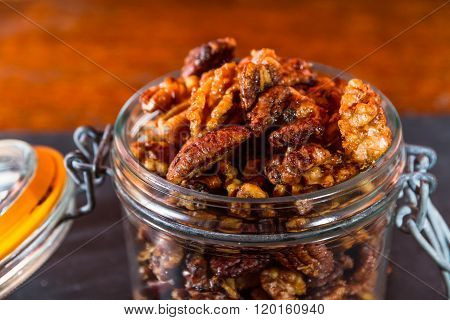 Pecan nuts and walnuts roasted with garlic and rosemary in a jar. Dark background closeup.