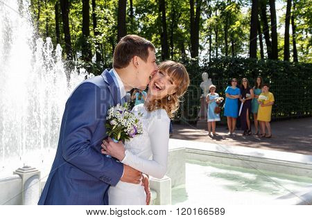 Groom And Bride Kissing Near A Fountain In Front Of Group Of Spectators