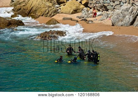 MEDITERRANEAN SEA. 30.04.2011. Costa Brava, Spain. Divers preparing to dive into the sea. A group of divers in a diving suit, standing in the water, ready to dive in turquoise waves of the Mediterranean