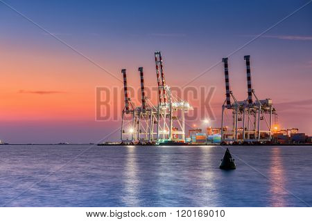 Unloading Container Of Cargo Ship Terminal At Twilight Scene.