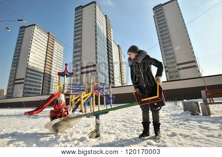 A Woman With A Baby In A Swing In A Winter Sunny Day.